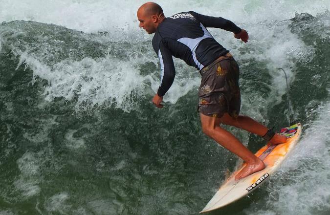 Ein geübter Eisbach-Surfer an der berühmten Eisbachwelle im Englischen Garten in Aktion