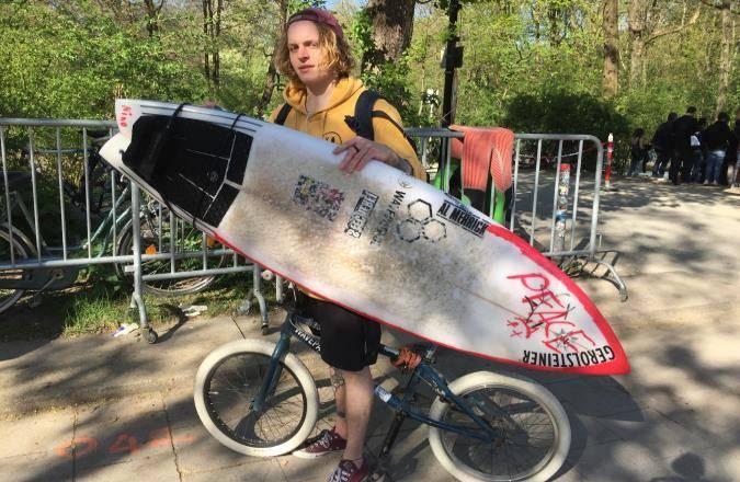Eisbach-Surfer mit Surfbrett auf dem Fahrrad